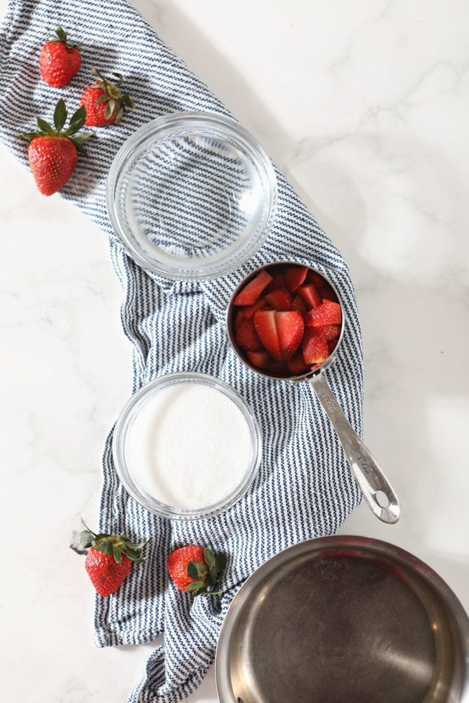 Ingredients for strawberry simple syrup in measuring cups on a blue striped towel