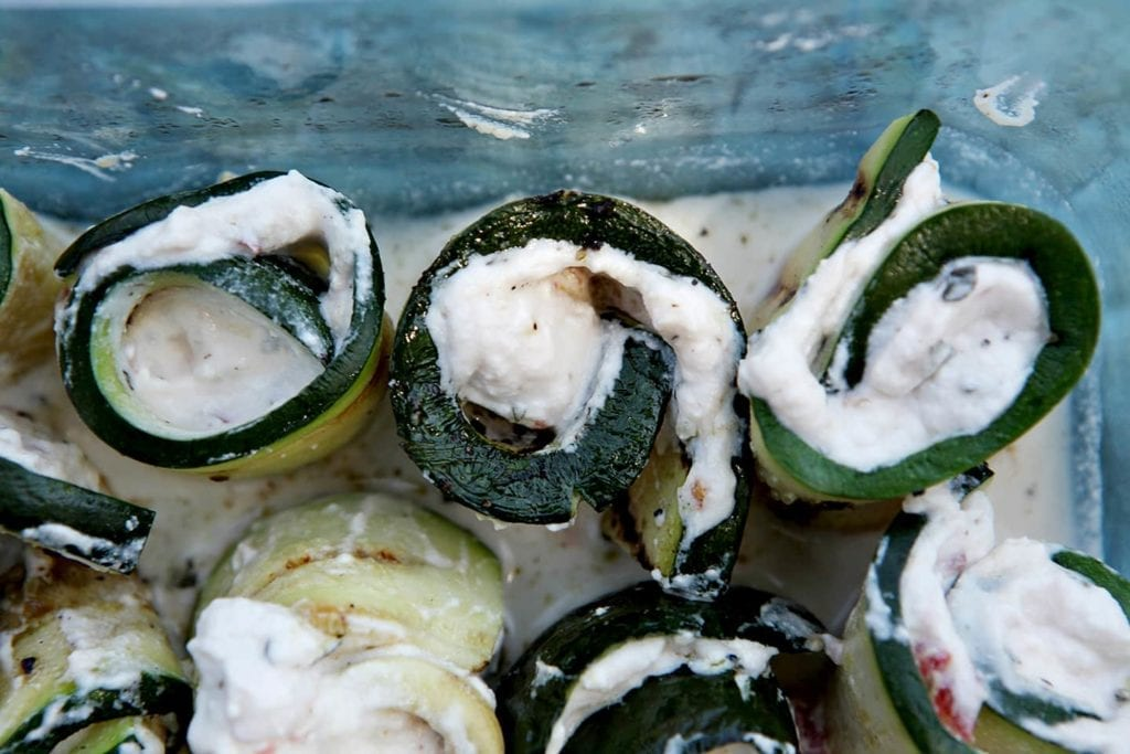 Grilled Zucchini Rollatini are the perfect finger food for a picnic or outdoor soiree! Zucchini is sliced thin and grilled after being brushed with olive oil and seasoned with salt and pepper. Once grilled, the zucchini is chilled. Brush on basil-seasoned ricotta cheese with tomatoes, then roll the zucchini up into bite-sized pieces. Chill until it's time to eat, then enjoy. These Grilled Zucchini Rollatini make for a scrumptious summertime vegetarian appetizer or entree!
