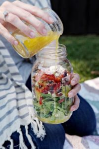 A woman pours dressing into a Strawberry Romaine Salad in a Jar while sitting on a picnic blanket