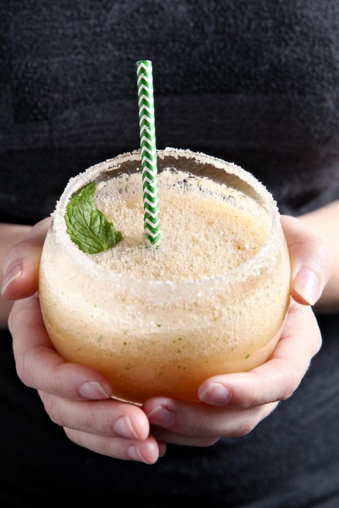 A woman holds a Cantaloupe Mint Margaritas, garnished with a sprig of mint and rimmed with sugar, before drinking