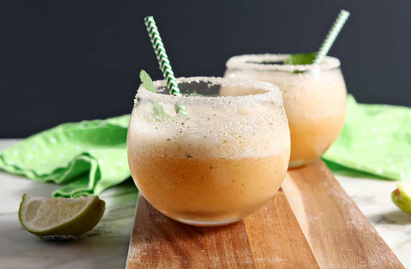 Two Margaritas are served on a wooden serving platter with lime wedges, rimmed with sugar, and garnished with mint