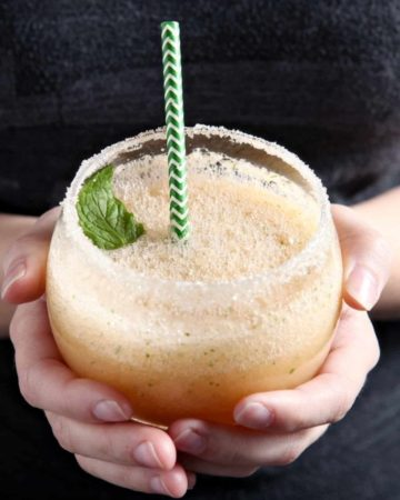 A woman holds a Cantaloupe Mint Margarita, rimmed with sugar and garnished with a sprig of mint, in hand before drinking