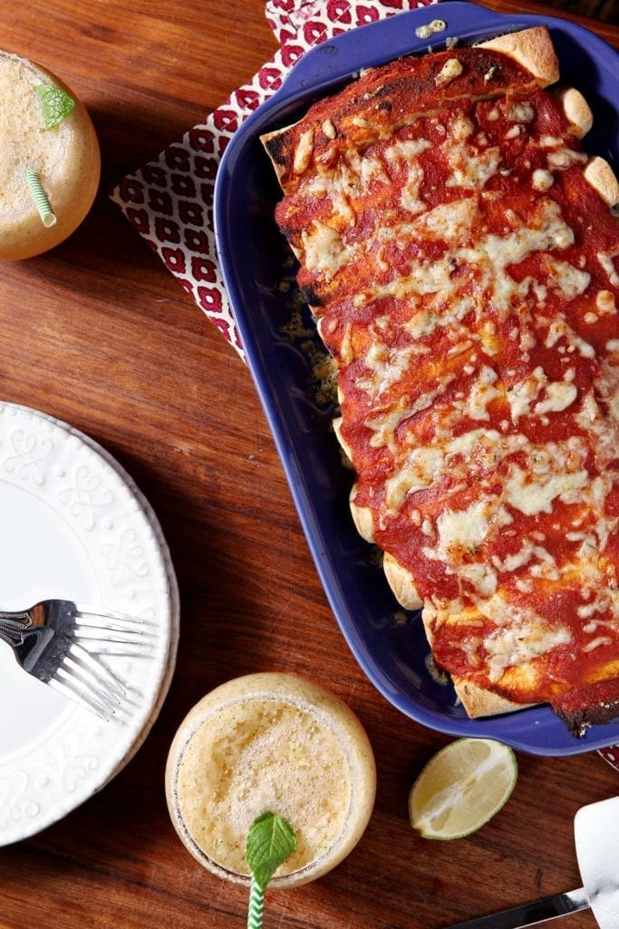 Pork Carnitas Enchiladas are a delicious entree for any Cinco de Mayo get-together! Pork simmers in the slow cooker on low all day, then is sautéed with onion and green chiles. Once the filling is complete, roll it up in tortillas with some pepperjack cheese, slather them in spicy enchilada sauce and bake for this spectacular dish!