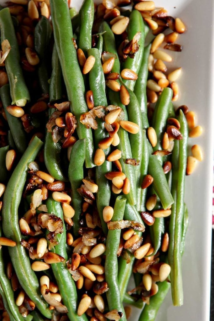 Close up of steamed green beans with pine nuts on a white platter from above