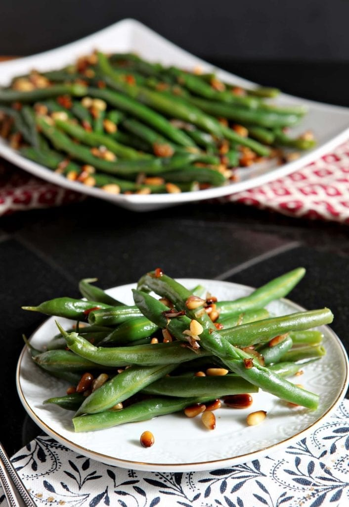 Toasted Pine Nut Green Beans make the BEST accompaniment for any weeknight meal! Steamed green beans are topped with toasted pine nuts and a diced shallot, then drizzled with olive oil. This vegan side dish is sure to be a winner at the dinner table.