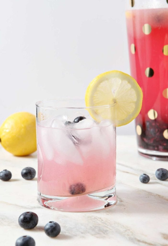 A glass of homemade blueberry lemonade with a lemon slice in front of a pitcher