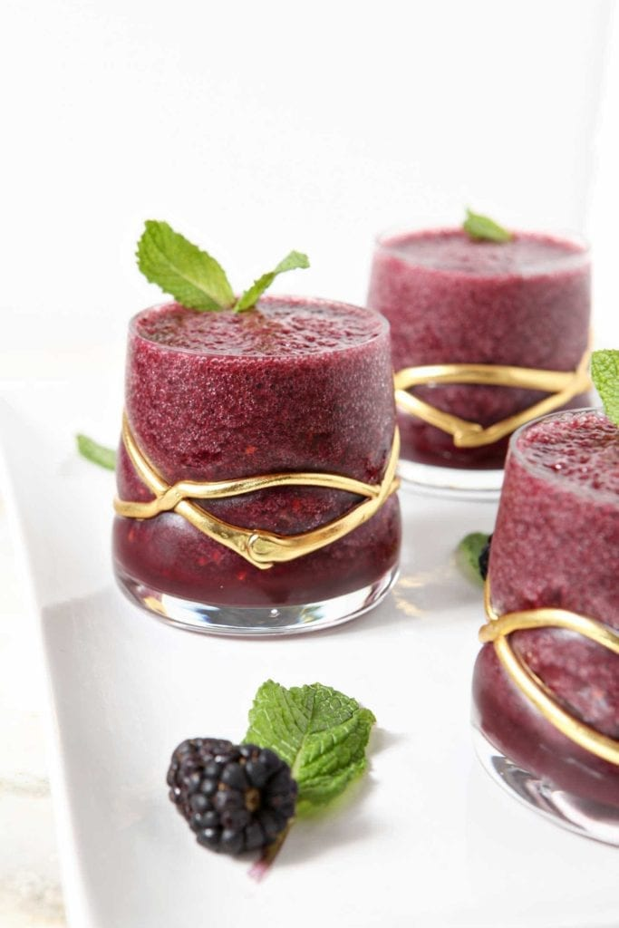 Three glasses of blackberry gin slushes with mint and berry garnish