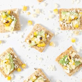 Cotija Corn Avocado TRISCUIT Crackers -- CotijaCornOcadoScuits -- are the perfect summertime appetizer! Corn is boiled in its husk, then grilled for a lovely char. An avocado is sliced. Cotija cheese is crumbled. TRISCUIT Original Crackers are topped with an avocado slice, the corn kernels and the cotija before being devoured. This savory, slightly salty appetizer makes a tasty vegetarian starter for any crowd this season! #ad #TRISCUITSummer