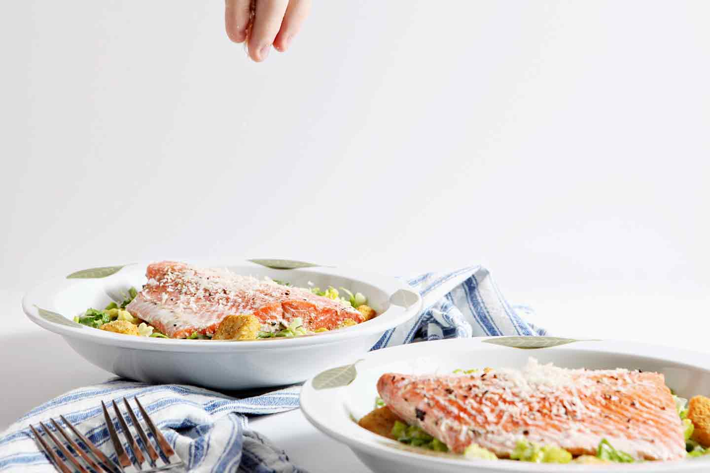 Oven Poached Salmon Caesar Salads being sprinkled with additional parmesan cheese before serving