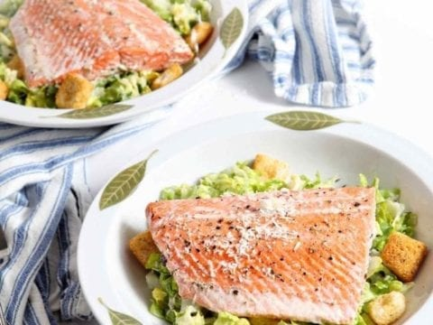 Image of two Oven Poached Salmon Caesar Salads on a white background with a blue-and-white striped towel