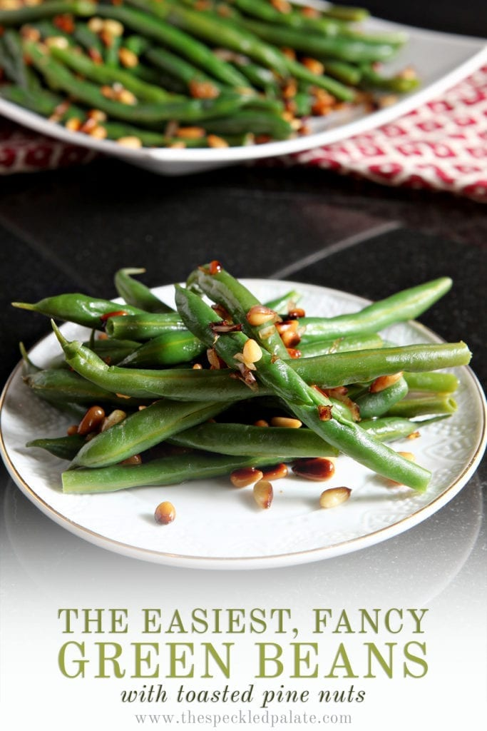A white plate holds a serving of Vegan Green Beans with Toasted Pine Nuts and shallots with the text 'the easiest, fancy green beans with toasted pine nuts'