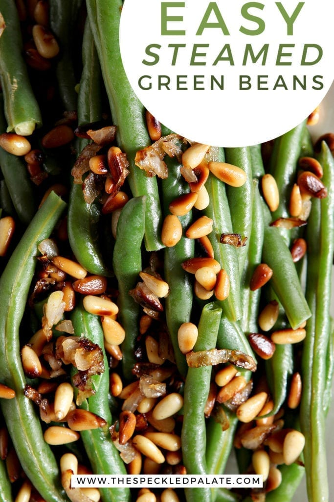 Close up of a platter holding Vegan Green Beans garnished with Toasted Pine Nuts and shallots with the text 'easy steamed green beans'
