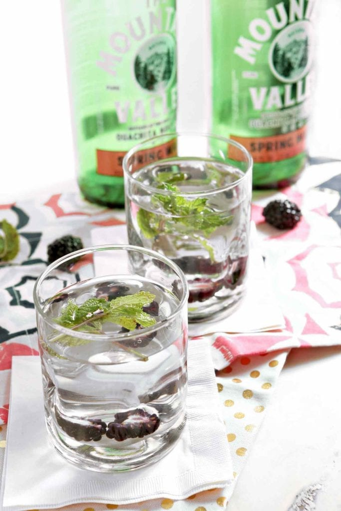 Cool down this summer with homemade Blackberry Mint Spa Water, made with Mountain Valley Spring Water. This spa water is so simple to make any day this season. Bottles of Mountain Valley Spring Water are poured into a pitcher, then mint sprigs and sliced fresh blackberries are added. Stir, then refrigerate for at least an hour. This spa water is refreshing and the perfect way to stay hydrated on a warm summer's day! #ad #NaturalAmericanGoodness