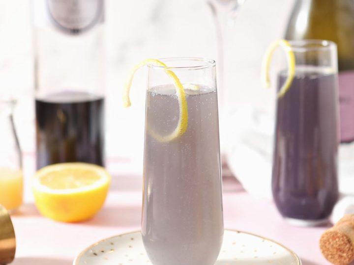 A creme de violette drink sits on a gold plate