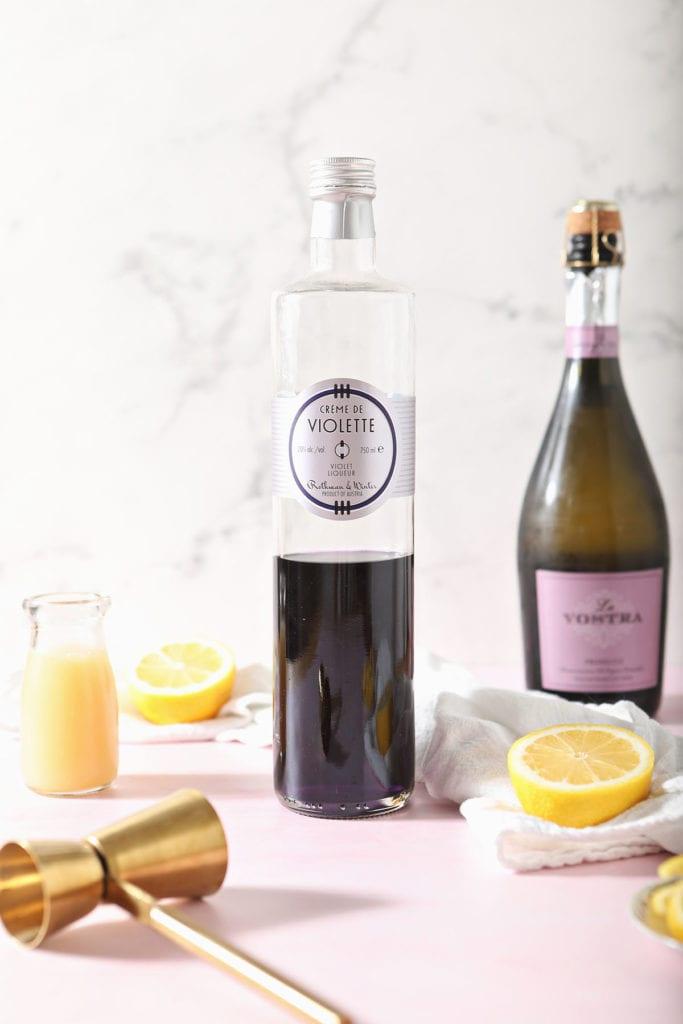A bottle of creme de violette sits next to lemon juice, champagne and lemons