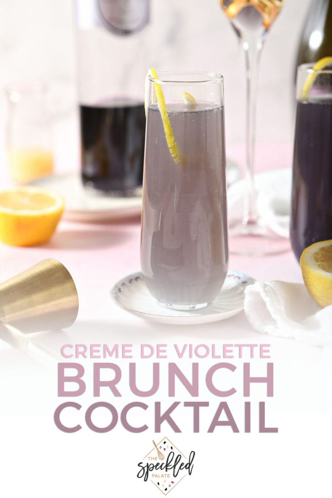 A purple champagne cocktail sits on a plate with the text 'creme de violette brunch cocktail'