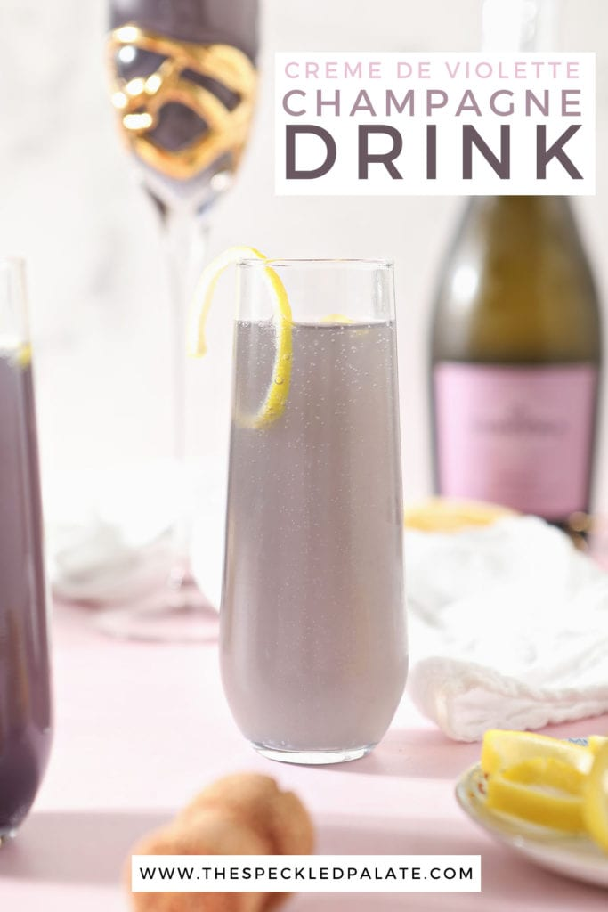A champagne flutes holds a purple drink garnished with a lemon twist with the text 'creme de violette champagne drink'