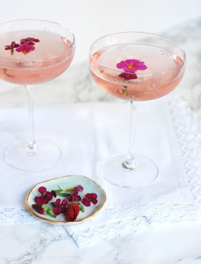 Two glasses of drinks with flower garnish