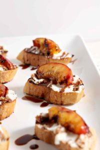Grilled Peach Bruschetta sit on a white platter, drizzled with a balsamic reduction, before serving