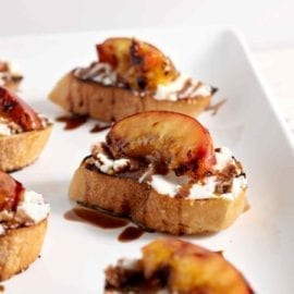 Grilled Peach Bruschetta is a perfect sweet appetizer or dessert for the summertime. Fire up the grill, slice and pit a few fresh peaches, brush the peaches with a little bit of olive oil, then grill until the sugars in the fruit caramelizes. Grill the bread, too. When both are done, smear the bread with fresh ricotta cheese, place the peach slices on top of the cheese, then drizzle with a balsamic vinegar reduction for the final touch. Perfect!