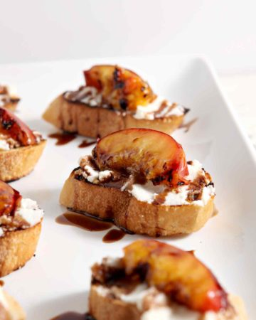 Grilled peaches sit on top of ricotta crostini on a platter