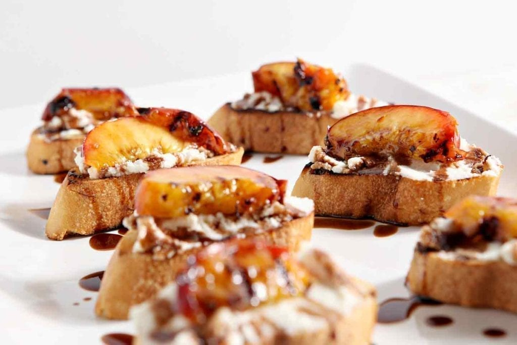 Grilled peaches on top of ricotta crostini