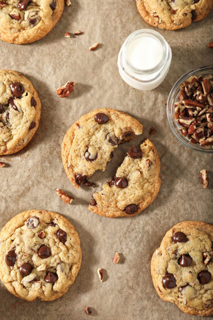 Classic Pecan Chocolate Chip Cookies on a pan with a glass of milk and pecan pieces