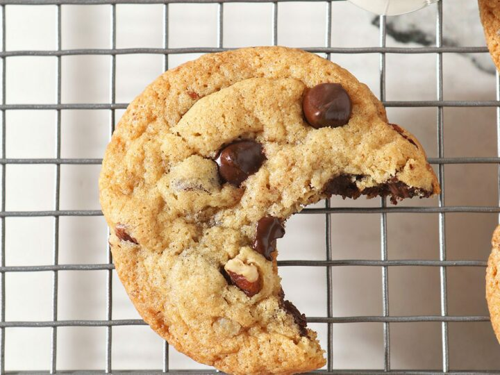 A bitten-into chocolate chip cookie on a cooling rack