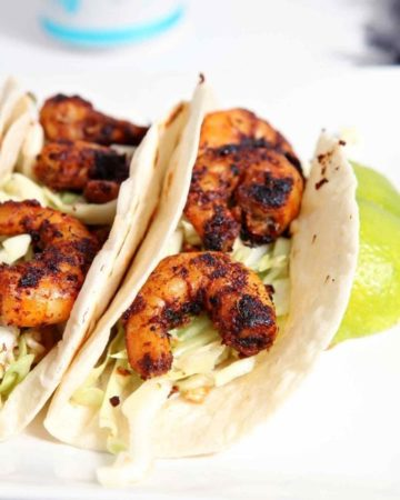 Blackened Shrimp Tacos with a crunchy coleslaw are the BEST entree to make at your football tailgate! Shrimp are liberally sprinkled with homemade blackening seasoning, then cooked. Flour (or corn!) tortillas are warmed on the grill. When the elements of the dish are ready, the shrimp are served atop a (made-at-home) Asian-inspired coleslaw that features green cabbage, toasted almonds, toasted Ramen noodles and a honey vinaigrette. These Blackened Shrimp Tacos go great with beer and are easily transported as you peruse your team's tailgate scene!