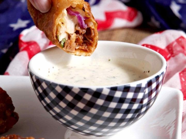 A half-eaten Pulled Pork Coleslaw Eggroll is dipped into the dipping sauce