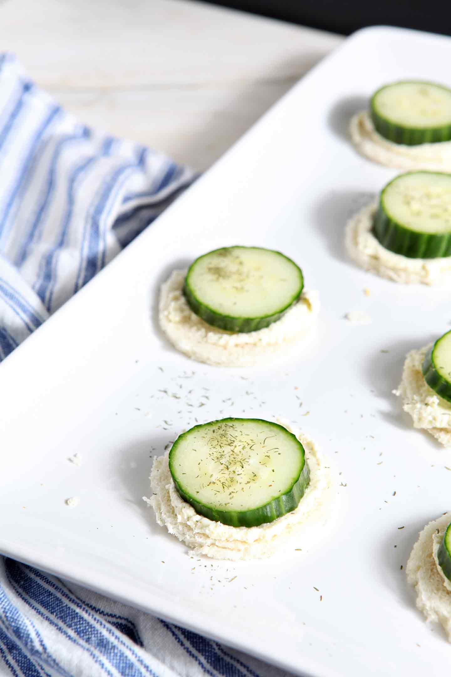 These aren't your mama's Cucumber Finger Sandwiches! These sandies are a twist on the classic baby and bridal shower finger food. Instead of the traditional mayonnaise-based spread, this recipe calls for a whipped feta and cream cheese spread, studded with dill. Cut your thinly sliced bread into the desired shape, slather with the whipped feta and cream cheese spread, top with a English cucumber slice, sprinkle with dill, and you're good to go!