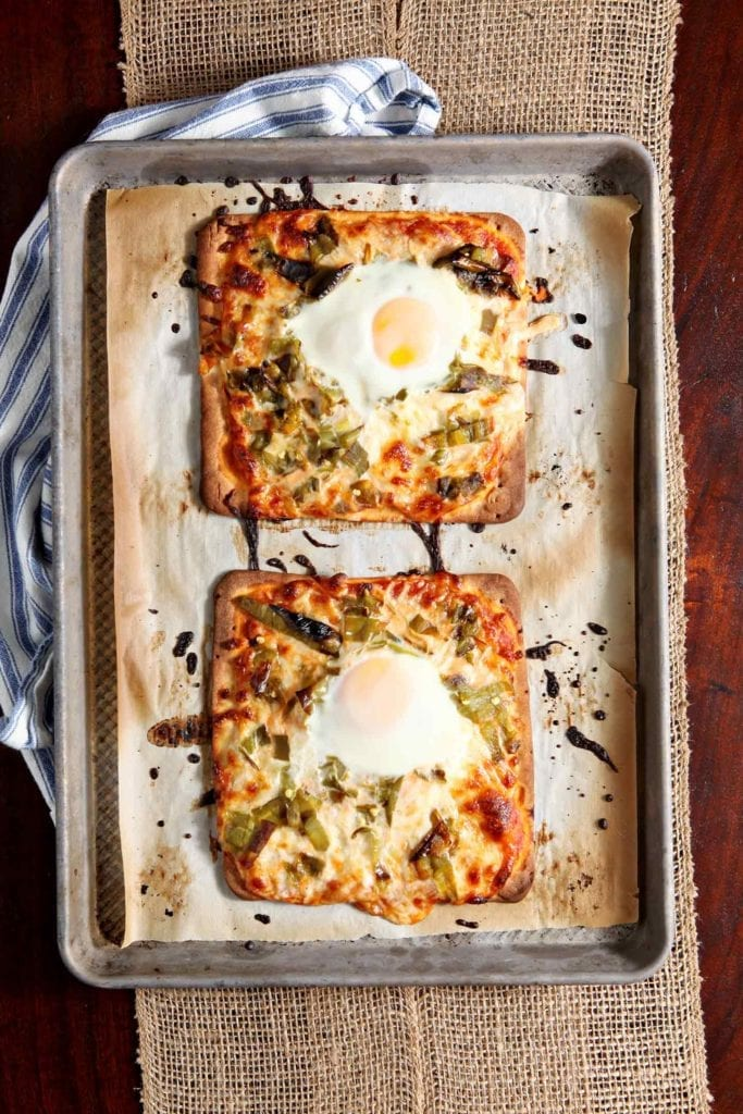Two Hatch Chile Breakfast Flatbreads sit on a baking sheet, straight out of the oven.