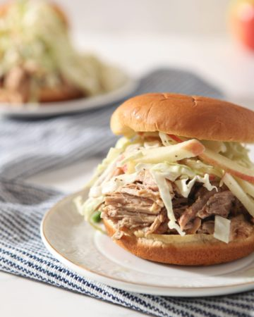 Close up of an Apple Cider Pulled Pork Sandwich with slaw on a white plate on top of a blue striped towel