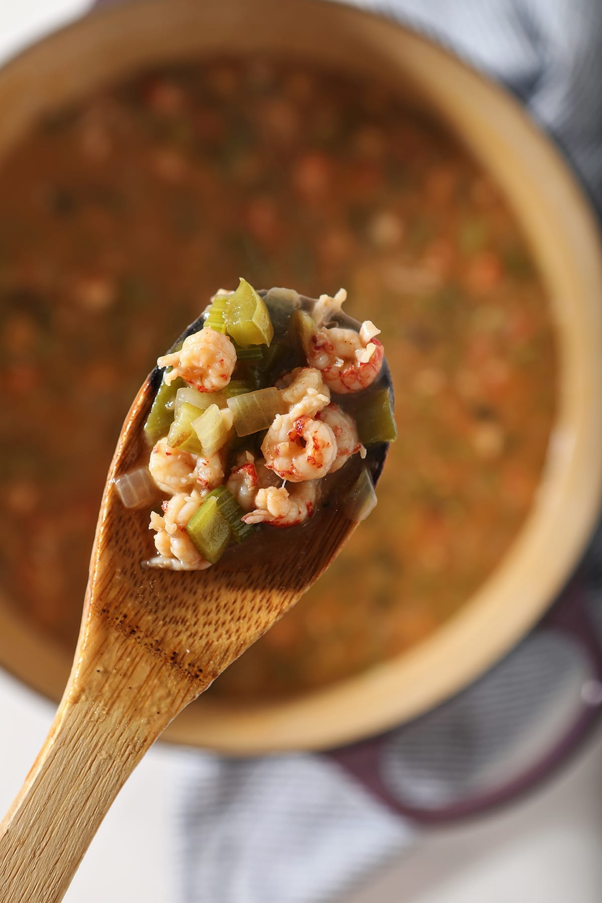 A wooden spoon holds crawfish tails and other etouffee ingredients