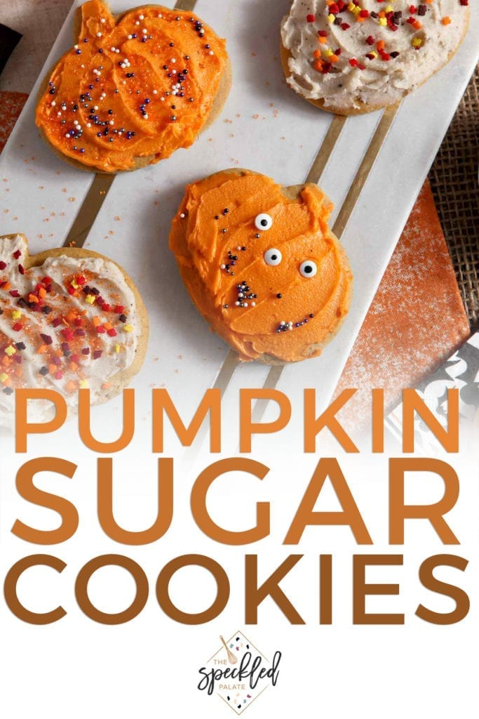 Decorated pumpkin cut out cookies sit on a marble slab with the text 'pumpkin sugar cookies'