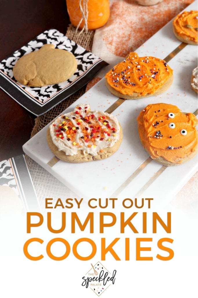 Decorated Pumpkin Sugar Cookies sit on a marble slab next to an undecorated cookie and jars of icing with the text 'easy cut out pumpkin cookies'