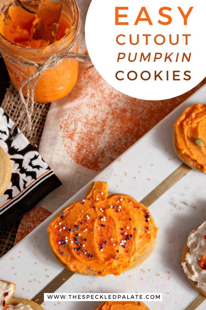 Close up of an orange iced pumpkin with sprinkles on a marble slab with the text 'easy cutout pumpkin cookies'