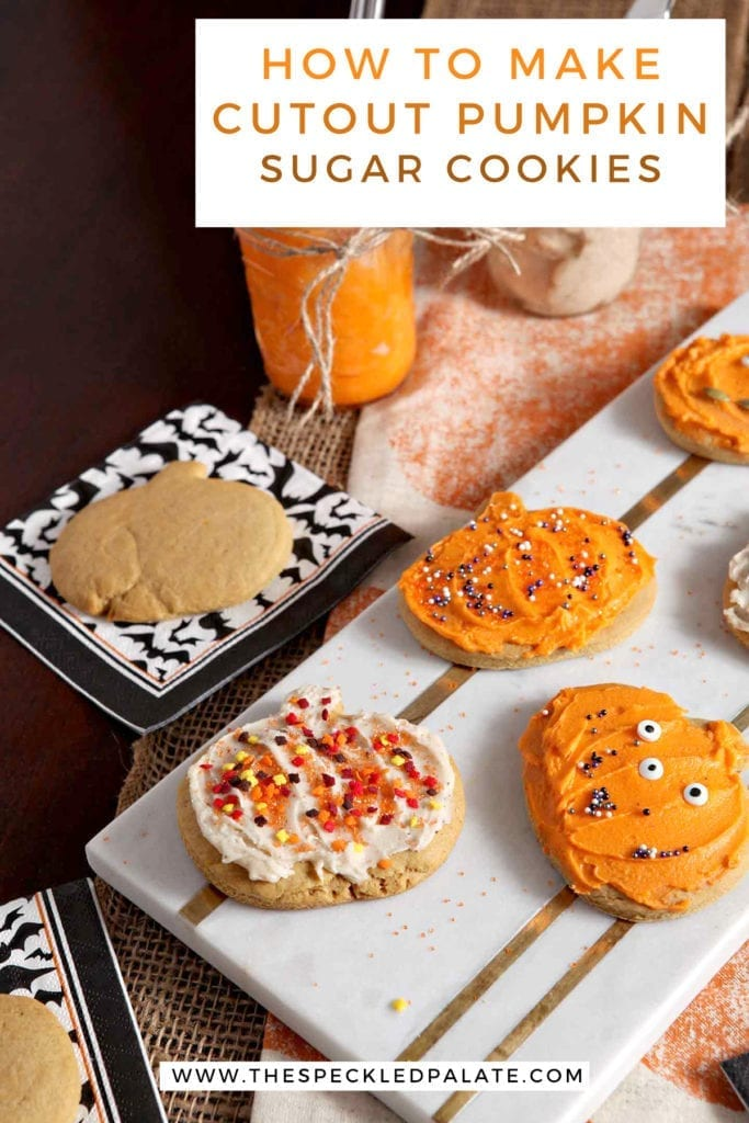 Decorated Pumpkin Sugar Cookies sit on a marble slab next to an undecorated cookie and jars of icing with the text 'how to make cutout pumpkin sugar cookies'