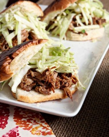 Three apple cider pulled pork sandwiches with apple coleslaw on a white platter on a table with fall decorations