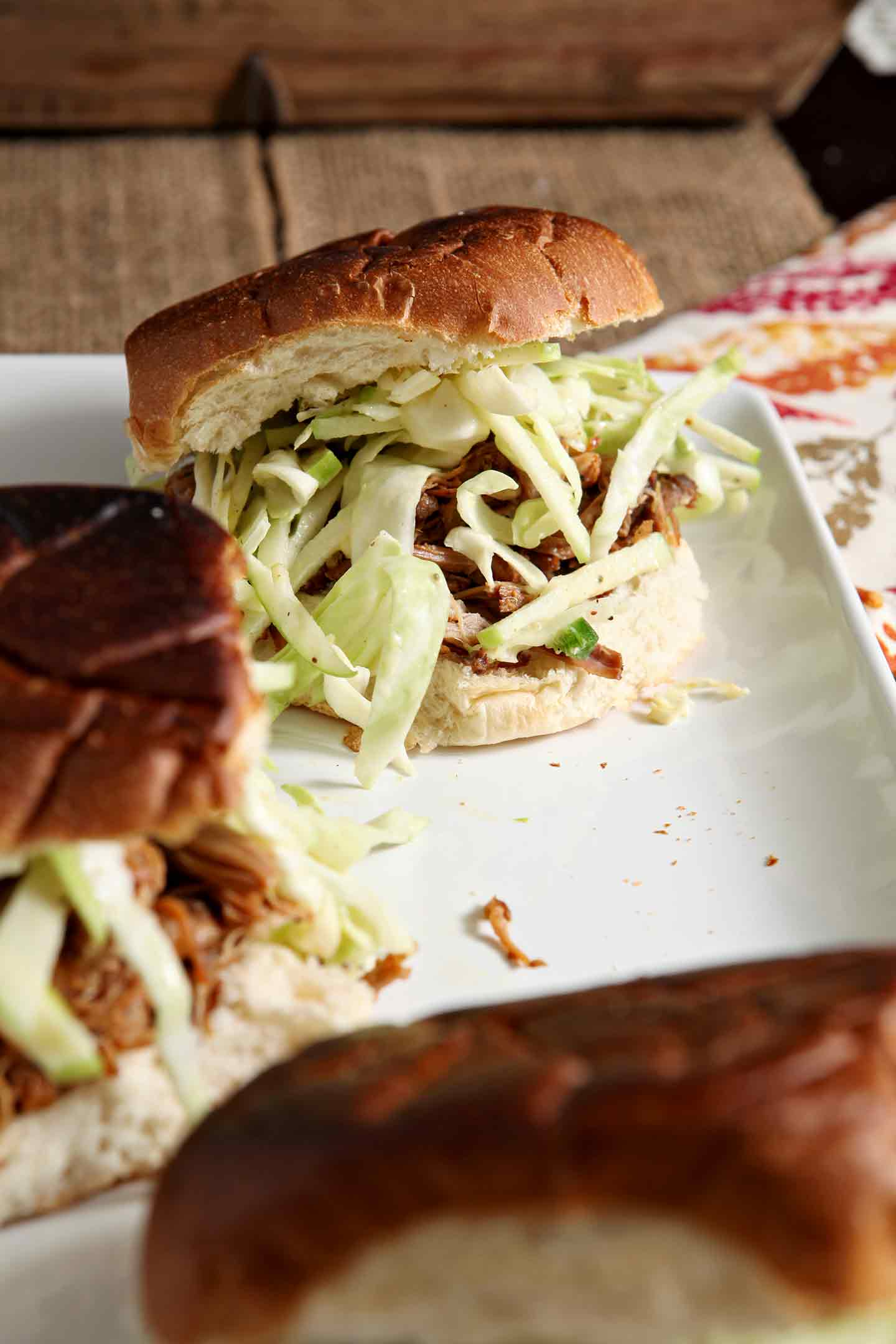 Pork and apples are an age-old combination... and this Apple Cider Pulled Pork with Apple Cabbage Slaw is the perfect entree for any fall get together or a simple weeknight meal. Pork butt simmers in spiced apple cider for hours in the slow cooker before shredding. Serve on a toasted bun with a tart apple cabbage coleslaw in a creamy yogurt sauce. Apple Cider Pulled Pork with Apple Cabbage Slaw makes a delicious meal for the whole family!