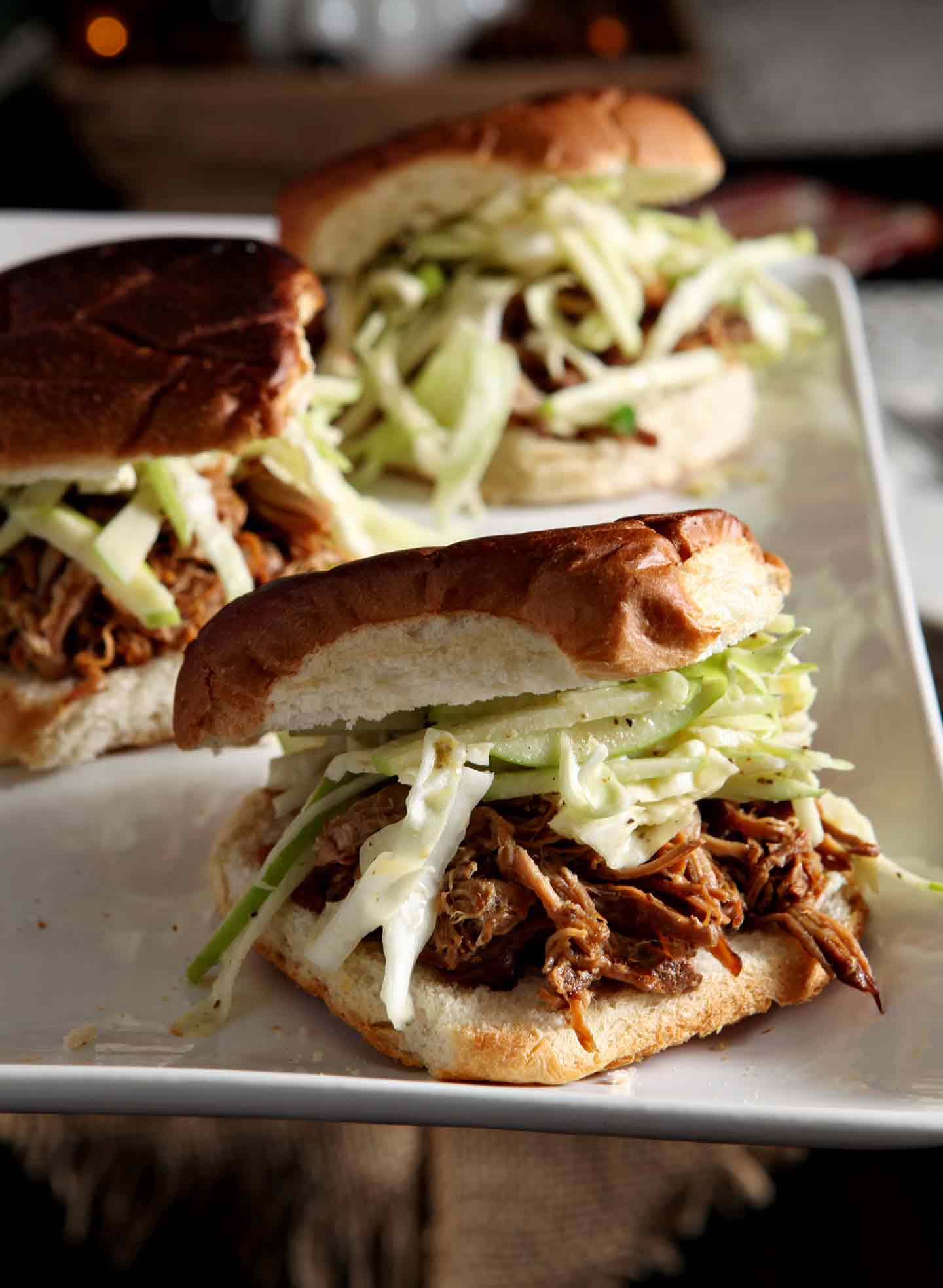 Three Apple Cider Pulled Pork with Apple Cabbage Slaw are served on buns on a white platter
