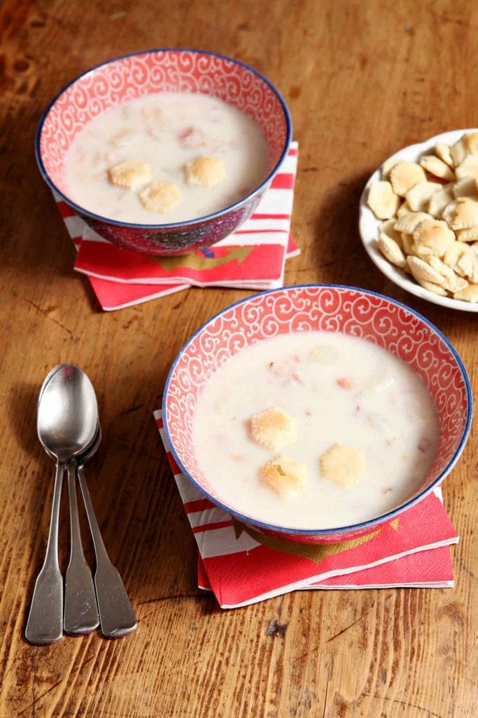 Two bowls of Bob\'s Bacon Potato Clam Chowder on wood table