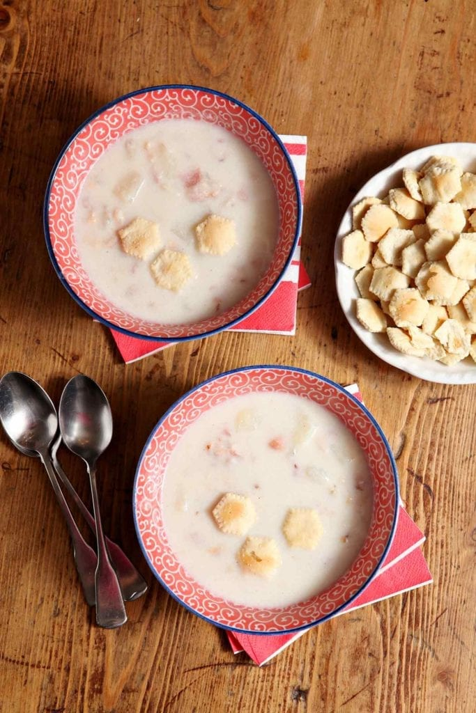 Overhead picture of 2 bowls of clam chowder on wood table