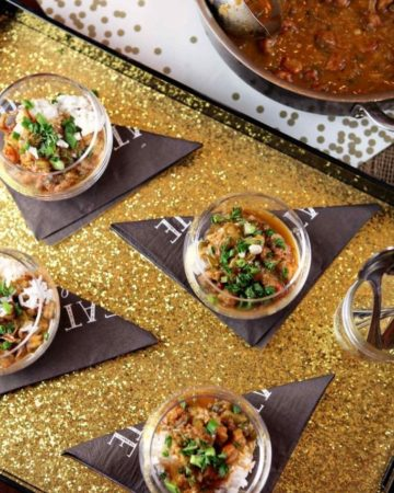 Overhead of four glasses holding crawfish etouffee garnished with parsley and green onions on a gold tray