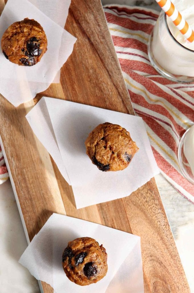 Mini Pumpkin Chip Muffins on a wooden board with milk from above