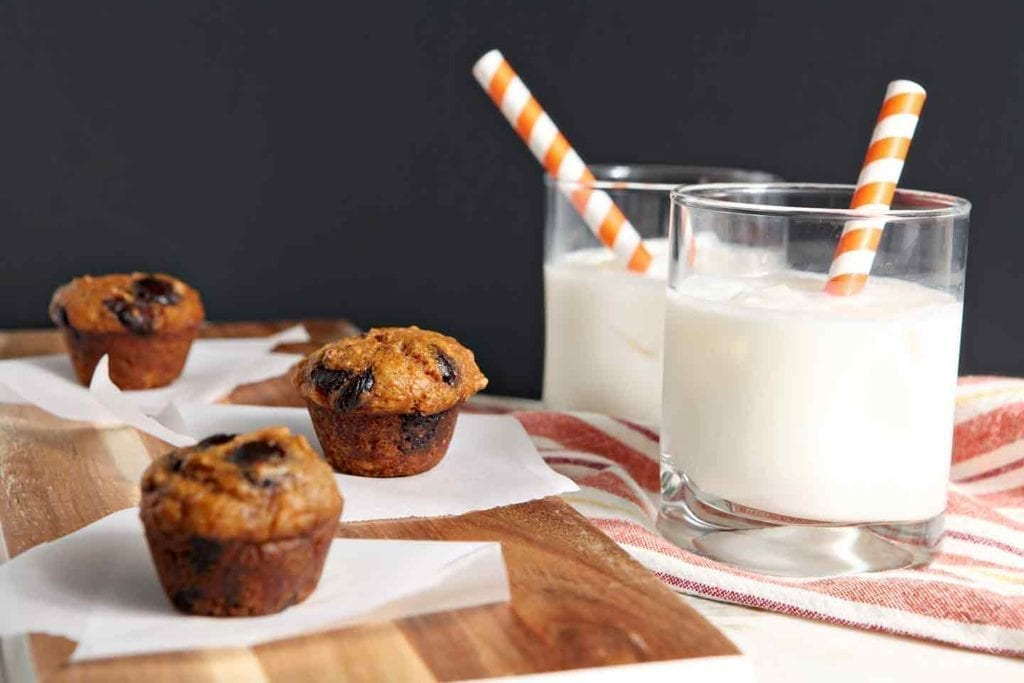 Mini Pumpkin Chip Muffins on a wooden board with milk