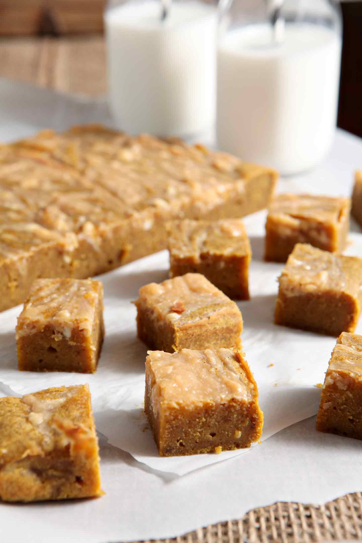 Sliced pumpkin blondies, from the side, with jugs of milk