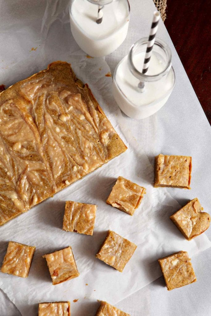 Overhead image of Pumpkin Blondies, partially sliced, and showing the cream cheese caramel swirl