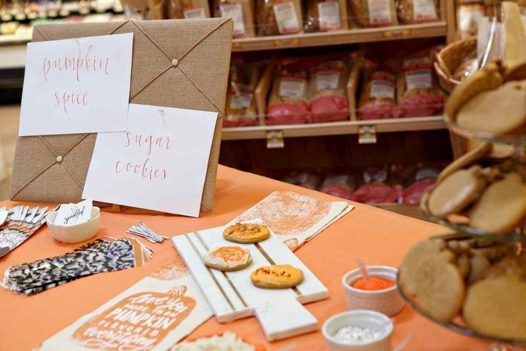 An orange-lined table inside a Sprouts with cookie decorating related items sitting on it
