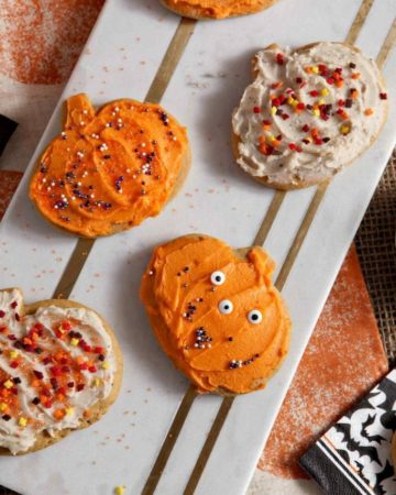 A marble tray holds several decorated Pumpkin Sugar Cookies with brown butter frosting